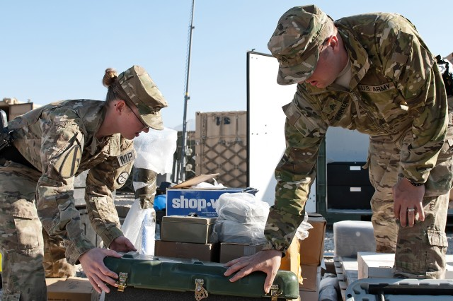 Sgt. Christopher C. Parker (right), a military police patrol supervisor, and Spc. Stephanie Brown (left), a traffic accident investigator, both in the 156th Military Police Detachment, attached to the 1st Air Cavalry Brigade, 1st Cavalry Division, inspect supplies that are being shipped back to the U.S,. as Soldiers of the 155th Inland Cargo Transfer Company, 10th Transportation Battalion, 7th Sustainment Brigade prepare to redeploy back to Fort Eustis, Oct. 24, 2011. Customs checks all equipment and supplies that are to be shipped back to the U.S. and are one of the many responsibilities of the 156th MP here.