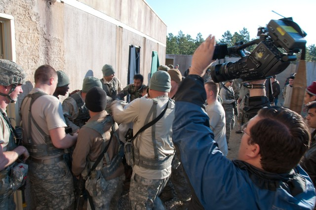 A mock riot breaks out among role players playing Afghan soldiers and villagers during a field training exercise conducted by the 82nd Airborne Division's 1st Brigade Combat Team Oct. 27, 2011, at Fort Bragg, N.C.  At right is a broadcast journalist from television station WTVD of Raleigh who is reporting on the training.  (U.S. Army photo by Sgt. Michael J. MacLeod)