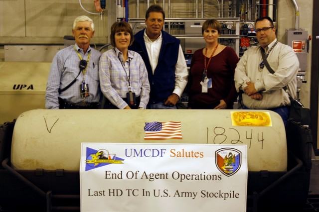 From left, Leland Guthmiller, area supervisor, Kim Jackson, operations manager, Ted Pappas, assistant operations manager, Surety, Heather Callihan, special projects shift superintendent, and Mike Eff, with special projects, stand with the last mustard ton container in the Umatilla Chemical Depot stockpile.