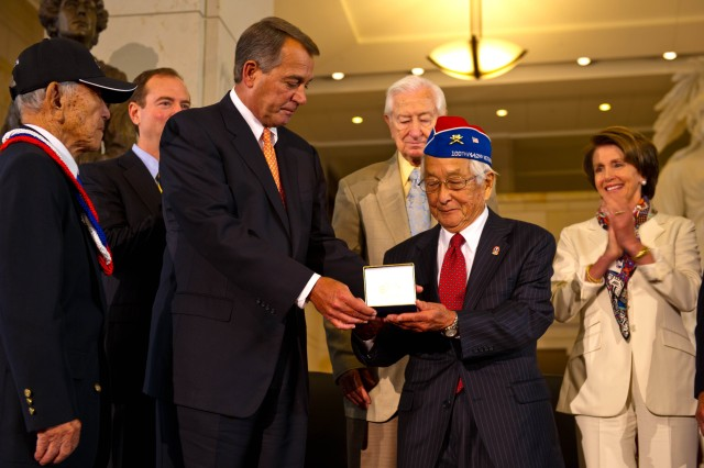 The Honorable John Boehner, the Speaker of the U.S. House of Representatives presents the Congressional Gold Medal to one of the three representatives from the 100th Infantry Battalion, 442nd Regimental Combat Team and the Military Intelligence Service.