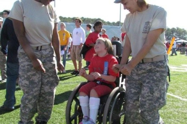 Columbia High School JROTC cadets Matisha Gaillard, left, and Monica Humbyrd dance with Jane Kielsmeier, a special needs student at Challenger Elementary School, during a break in the sporting events. Jane is the daughter of Darin and Angie Kielsmeier, who both work at Redstone Arsenal.