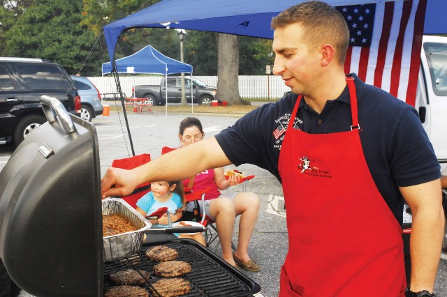 Capt. Daniel Cauthen, with the Maneuver Career Captains Course, grills during the tailgate before the Doughboy Bowl.
