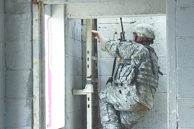 Sgt. Robert Everett climbs a ladder in an urban environment while holding on to his weapon at Fort Benning, Ga.