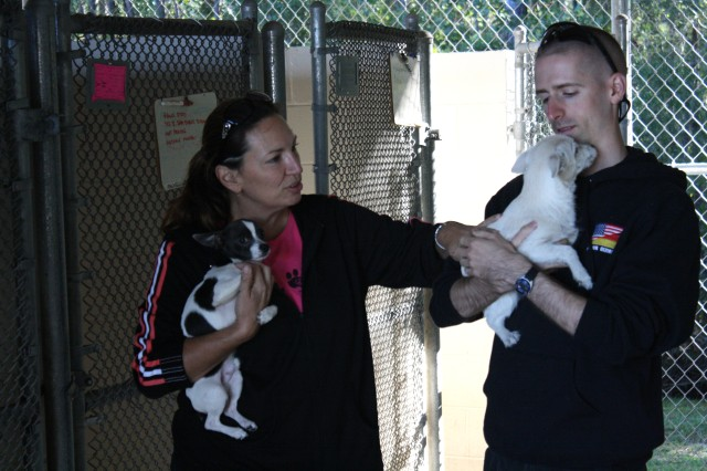 Specialist Branden Gums, a transportation logistics coordinator assigned to the 90th HRC, STB, 3rd Sust. Bde., 3rd Inf. Div., and Joy Bohannon, the CEO of Georgia Animal Rescue and Defence, rescue two puppies from the Fort Stewart Veterinary Clinic, Oct. 17.