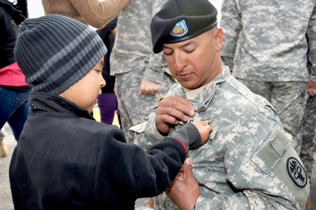 Four-year old Sean Leyva pins Air Assault wings on his father, Staff Sgt. Juan Leyva, noncommissioned officer in charge at CRDAMC's Thomas Moore Health Clinic, during a graduation ceremony at Fort Hood Oct. 28. Leyva was one of six CRDAMC Soldiers out of 241 candidates to earn their wings at Fort Hood's first air assault class. (U.S. Army photo by Patricia Deal, CRDAMC Public Affairs)