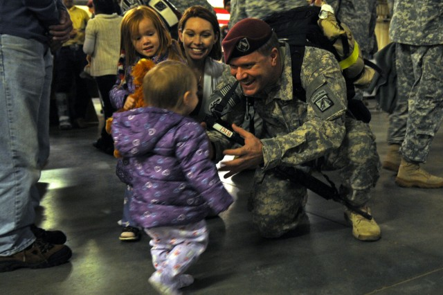 Staff Sgt. Michael Bernquist, XVIII Airborne Corps, holds his arms out for his daughter Evelyn, 1, after returning from a 12-month deployment to Iraq, at Fort Bragg, N.C., Nov. 4, 2011. Bernquist was also greeted by his wife, Brandi, and older daughter Brooke, 4, at the welcome home ceremony.