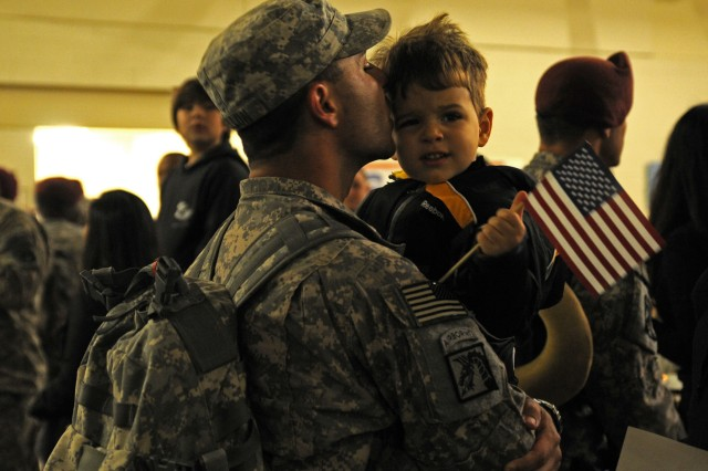 A Soldier, with XVIII Airborne Corps, kisses his son after being reunited after his 12-month deployment to Iraq, at Fort Bragg, N.C., Nov. 4, 2011.