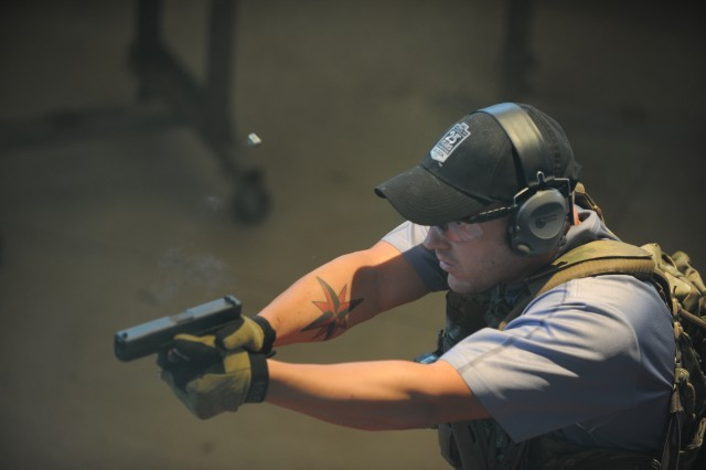 Sgt. 1st Class Drew Penny, 5th Special Forces Group, takes aim during a marksmanship challenge. Contestants competed in a variety of firearms challenges such as target recognition and combat pistol.