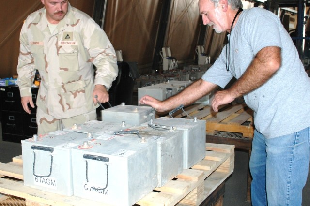 Michael Rogers and Dennis Hinds, Tank Automotive-Armament Command, inspect a new shipment of old batteries as they arrive at Camp Arifjan, Kuwait. The batteries are used in all tactical vehicle platforms from tanks to trucks.
