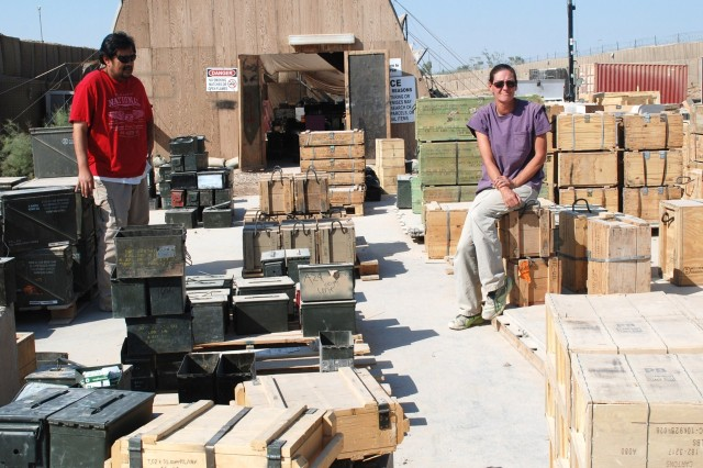 Rodney Stingerie and Suzanne Greenway, 402nd Army Field Support Brigade, survey the ammo lot at Camp Liberty, Iraq as units from surrounding FOBs arrive in a steady stream to unload ammunition prior to departing the country.