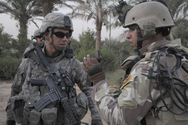Cpl. Hassen Anad (right) of 4th Battalion, 24th Brigade, 6th Iraqi Army Division shows 1st Lt. Charles Franz a platoon leader with, A Troop, 1st Squadron, 73rd Cavalry Regiment, 2nd Brigade of the 82nd Airborne Division a magazine to a confiscated weapon Oct. 24 in Mansour District, Iraq. 2/82 is working with Iraqi Security Forces to enable the safe withdrawal of thousands of Soldiers and pieces of equipment. Franz is a native of Flagstaff, Ariz.