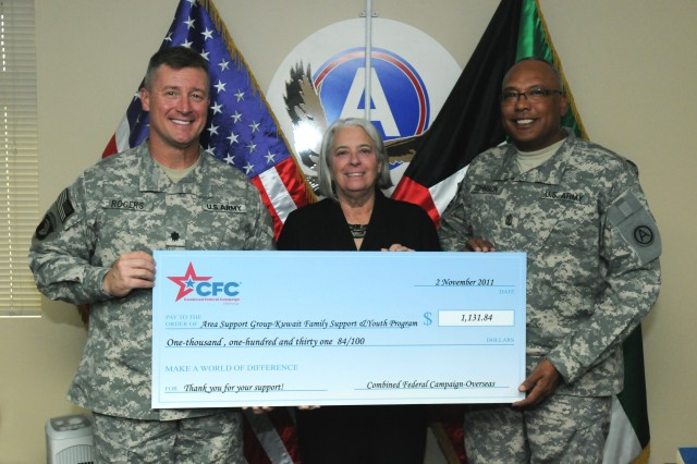 """CAMP ARIFJAN, Kuwait - Lt. Col. John Rodgers, garrison commander, Area Support Group """" Kuwait (left) and Tallahassee, Fla. native, and Sgt. Maj. Melvin Johnson (right), garrison sergeant major, Area support Group """" Kuwait, and Newport News, Va. native, is presented a check from Family Support and Youth Programs from Renee S. Acosta (center), Global Impact president and CEO. Global Impact is the Department of Defense campaign management organization for the Combined Federal Campaign """" Overseas. FSYP is one of the many charitable programs offered through CFC-O. Third Army's commitment to the well-being of its communities remains a priority and reflects the strength of our nation by providing charitable donations throughout the world."""