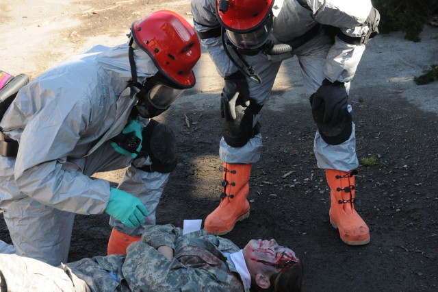 Kingston,N.Y.- Soldiers of the New York Army National Guard's  1156th Engineer Company in full Hazardous Material gear assist civilian participant during the extraction phase of a joint force first responders exercise in reaction to a radioactive attack. New York National Army and Airmen Guardsmen collaborate with local authorities to help train for the response to a radioactive terrorist attack, Nov. 5,2011.