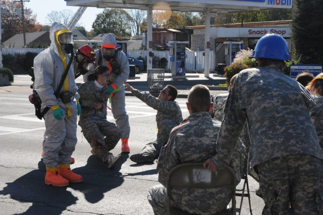 Kingston,N.Y.- Soldiers of the New York Army National Guard's 1156th Engineer Company in full Hazardous Material gear assist civilian participants during the extraction phase of a joint force first responders exercise in reaction to a radioactive attack. New York National Army and Airmen Guardsmen collaborate with local authorities to help train for the response to a radioactive terrorist attack, Nov. 6,2011.