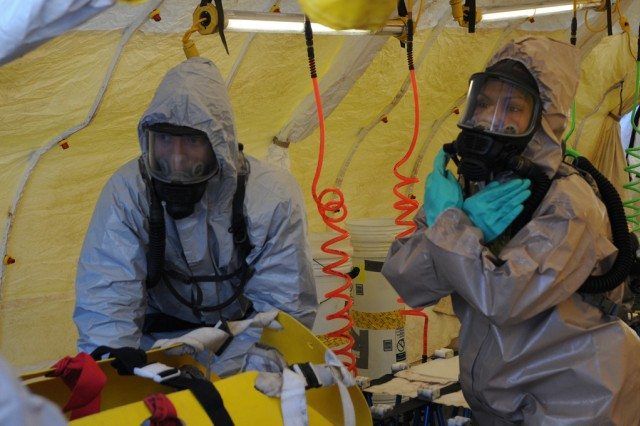 KINGSTON ,N.Y.- Soldiers from the 222nd Chemical Company in full Hazardous Material gear assist civilian participants during the decontamination phase of a joint force first responders exercise in reaction to a radioactive attack. New York National Army and Airmen Guardsmen collaborate with local authorities to help train for the response to a radioactive terrorist attack, Nov. 6,2011.