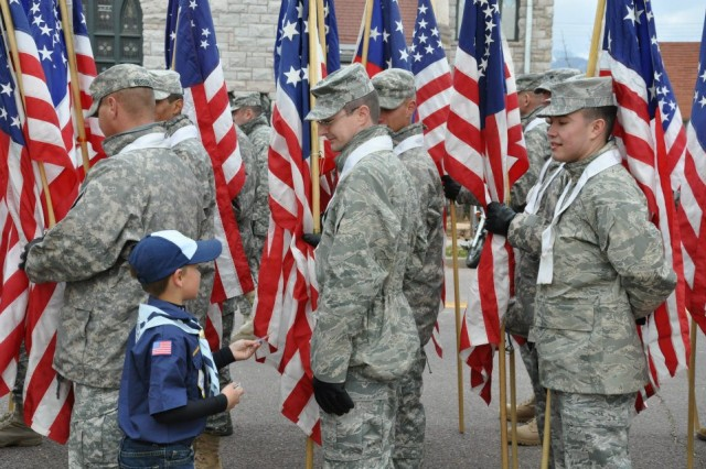 A local Cub Scout hands out thank you cards to the airman from the 21st Space Wing and Soldiers from the 1st Space Brigade who participated in the Flight of the Flags during the Veterans Day parade Nov. 5 in Colorado Springs, Colo.