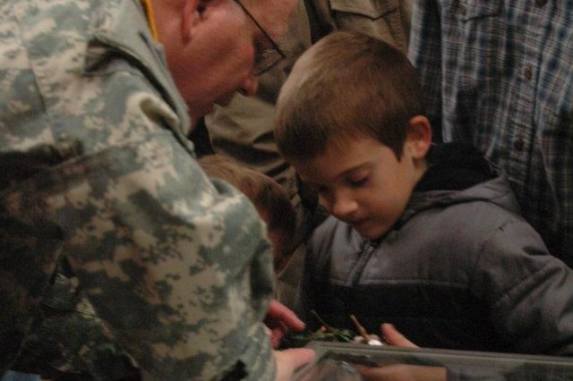 Lt. Gen. Richard P. Formica, U.S. Army Space and Missile Defense Command/Army Forces Strategic Command commanding general, talks with a boy about his toy tank during a guided tour of the Alabama Veterans Museum and Archives after the Veterans Day breakfast Nov. 5 in Athens, Ala.