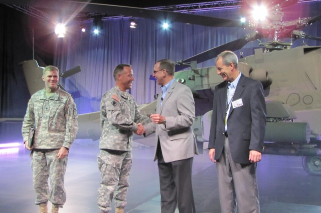Col. Shane Openshaw (middle left), Apache Helicopters project manager is shaking the hands and accepting the log book and keys from David Koopersmith (middle right), Boeing vice president for Attack Helicopter Programs. Left is Lt. Col. Dan Bailey, Apache Block III product manager and right is Scott Rudy, Boeing Apache Block III program manager.