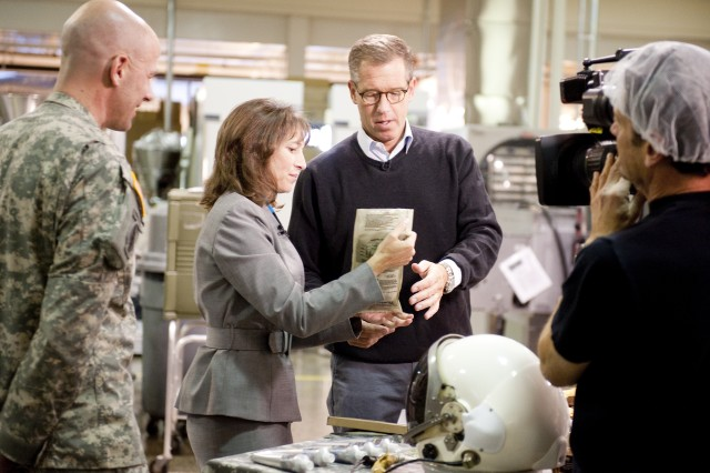 Brian Williams of NBC News talks with Lauren Oleksyk of the Department of Defense Combat Feeding Directorate on camera during a Nov. 4 visit to Natick Soldier Research, Development and Engineering Center. Lt. Col. Frank Sobchak, U.S. Army Garrison-Natick commander, left, looks on.