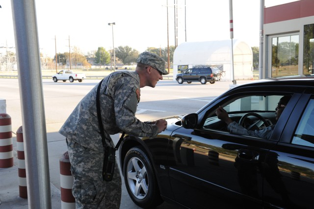 Pvt. 1st Class Bradley Manning checks the ID of a Fort Hood, Texas, Soldier entering the installation Nov. 1, 2011, at Fort Hood's Main Gate. Soldiers began augmenting Department of the Army security guards at Fort Hood access control points Oct. 31.