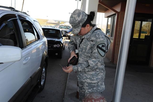 Sgt. Cynthia Melendez scans an ID card Nov. 1, 2011, at the main gate of Fort Hood, Texas.