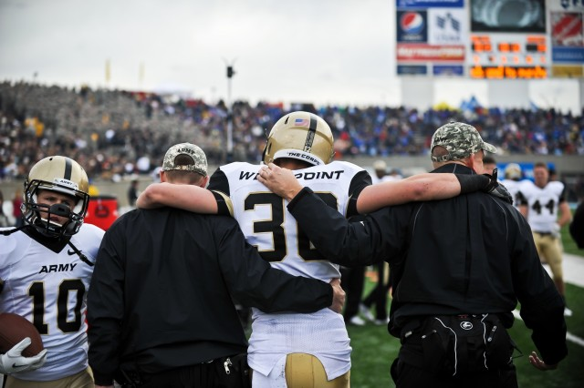 James Holland, a running back for Army Black Knights, is carried to the sideline by the coaching staff after suffering an injury during the Army vs Air Force game at the U.S. Air Force Academy in Colorado Springs, CO, Nov. 5, 2011.