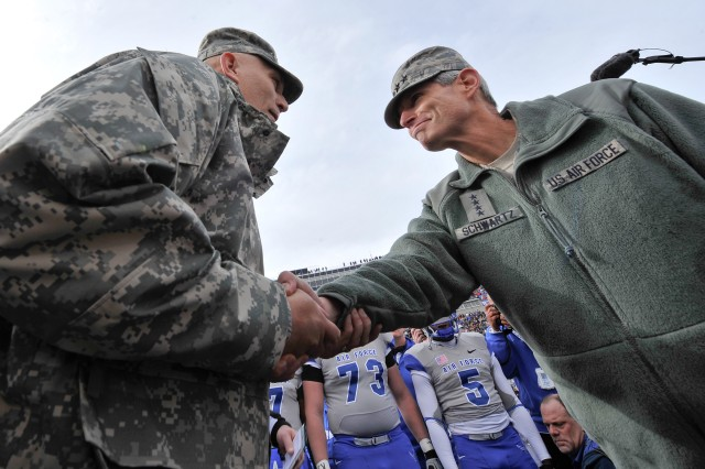 U.S. Army Chief of Staff Gen. Raymond T. Odierno shakes hands with Air Force Chief of Staff Gen. Norton A. Schwartz at Falcon Stadium prior to the start of the Army Black Knights versus the Air Force Falcons game at the U.S. Air Force Academy in Colorado Springs, CO, Nov. 5, 2011.