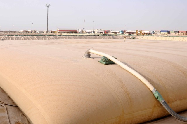 A large fuel bladder, nestled in a berm of earth, provides fuel for vehicles transporting equipment out of Iraq on Contingency Operating Base Adder, Nov. 5, 2011.