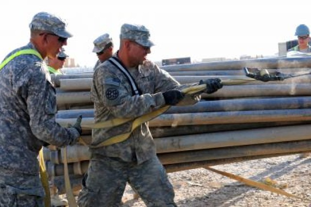 Soldiers from the 1729th Field Support Maintenance Company from Havre de Grace, Md., secure pipes to a forklift on Contingency Operating Base Adder, Iraq, Nov. 2, 2011.