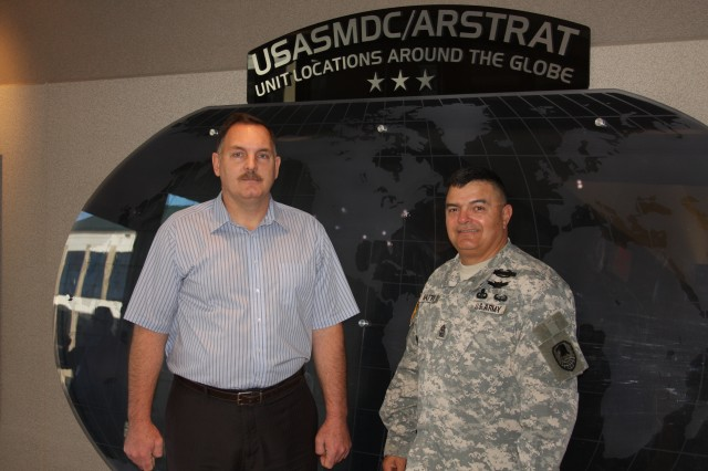 Retired Master Sgt. Mike Nash, left, U.S. Army Space and Missile Defense Command/Army Forces Strategic Command Office of Small Business Programs, and  Sgt. Maj. John Mattie, SMDC G-3, first served together as Soldiers during Operation Urgent Fury as the U.S. invaded Grenada in October 1983 and have been serving together at SMDC since 2008.