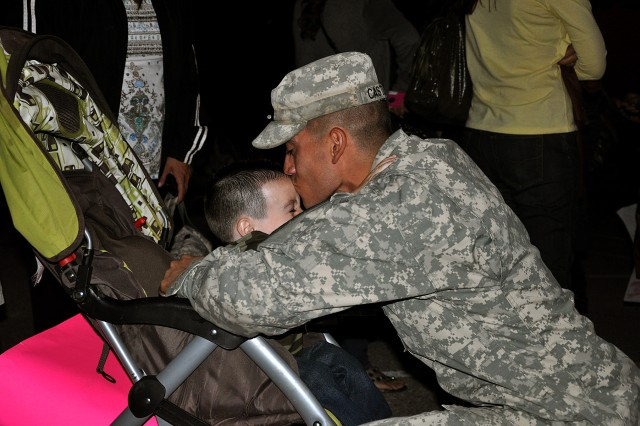 FORT HOOD, Texas--Pfc. Paul Castillo, Little Field, Texas, infantryman, Company B, 3rd Battalion, 8th Cavalry Regiment, 1st Cavalry Division, reunites with his family, hugs and kisses his son Jayce. More than 320 Warhorse Soldiers returned, Nov.2.