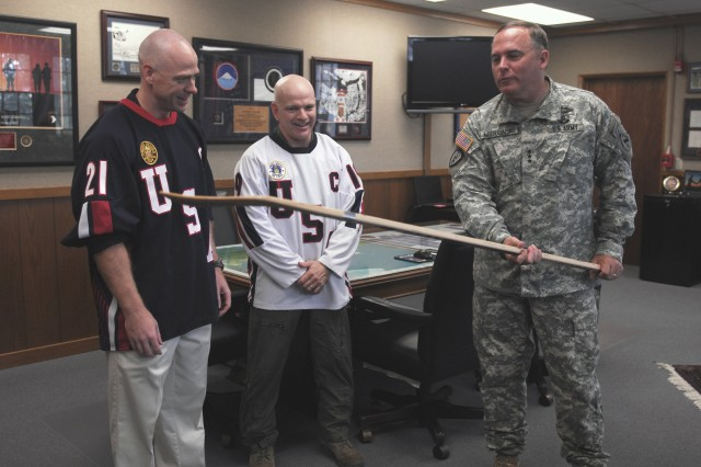 Lt. Gen. Francis J. Wiercinski looks at hockey stick presented to him by Air Force Lt. Col. Thomas A. Bell (center), captain of the Army, Air Force hockey team and Petty Officer 1st Class David Taylor (left), captain of the Navy, Marine Corps and Coast Guard hockey team present a hockey stick Nov. 8, to Lt. Gen. Francis J. Wiercinski, U.S. Army Pacific commander on behalf of the component commands across Oahu.
