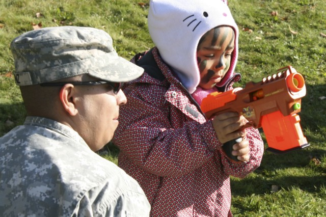 "A child practices herskills on the Nerf shooting range with the help from a Soldier during the 172nd Infantry Brigade's ""Deploy for a Day"" event."