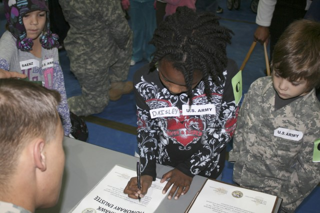 Children sign on the dotted line for their one-day contracts during in-processing.