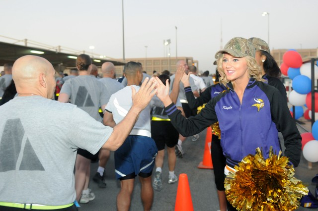 CAMP ARIFJAN, Kuwait - Kayla (right), Minnesota Vikings' cheerleader and Rochester, Minn. native, gives high fives and cheers on the runners/walkers during the Third Army 93rd birthday 5K run/walk here Nov. 7. Third Army and Morale, Welfare and Recreation's commitment to the well-being of its Servicemembers and civilians remains a priority. Through events like the 5K run/walk, Third Army is honoring its 93 years of achievements while keeping troops physically fit to sustain the fight and shape the future.