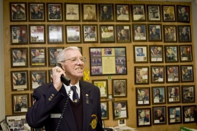 Retired Army Sgt. Maj. Ray Moran, who celebrates his 82nd birthday this week, talks on the phone with a prospective recruit in his office at Fort Meade, Md. His office wall documents the many Soldiers he has recruited over the decades.