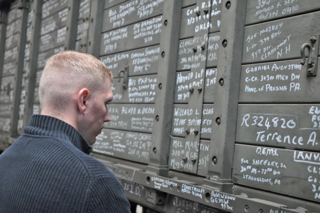 A visitor reads graffiti written on the side of a World War II U.S. Army cargo truck. Much of the graffiti was hand-drawn by American war veterans who have returned since 1994 to visit the area they liberated in September 1944.