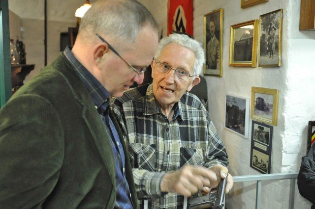 Marcel Schmetz, co-creator of the Remember Museum 39-45 in Thimister-Clermont, Belgium, shows a World War II German Army pistol to U.S. Army Brig. Gen. Ricky Gibbs, a 1st Infantry Division veteran and current V Corps commander, during a tour in September 2011.