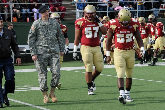 Air Force Col. Om Prakash, 82nd Training Wing vice commander, and Lt. Col. Mark P. Krieger, Jr. 1-17th Field Artillery Regiment commander, walk to midfield with Midwestern State football players to participate in the coin toss.