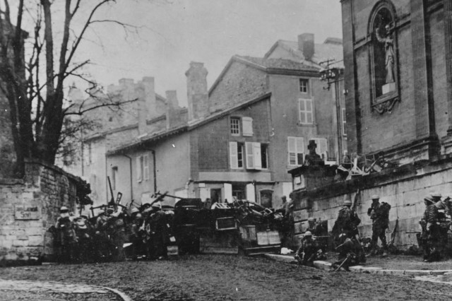 "Soldiers of the 353rd Infantry, near a church at Stenay, Meuse in France, wait for the end of hostilities. This photo was taken at 10:58 a.m., Nov. 11, 1918, two minutes before the armistice ending ""The Great War"" went into effect."