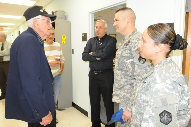 World War II veteran Frank Cupp, a former technical escort Soldier, talks to current technical escorts 1st Sgt. Rebeca Franco and Master Sgt. Terry Sykes, 22nd Chemical Battalion and Michael Rehmert (second from left), CBRNE Analytical and Remediation Activity, as well as Bill Brankowitz who interviewed Cupp on information from more than 60 years ago.