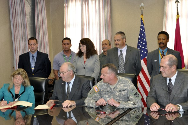 Contracting Chief Deborah Jones, l, validates the Memorandum of Agreement and makes the signing official.  Sitting from left watching Jones; Ed McCarthy, Arsenal deputy commander; Col. Mark F. Migaleddi, Arsenal commander; and Sam H. Kupresin, vice president of Mandus Group.