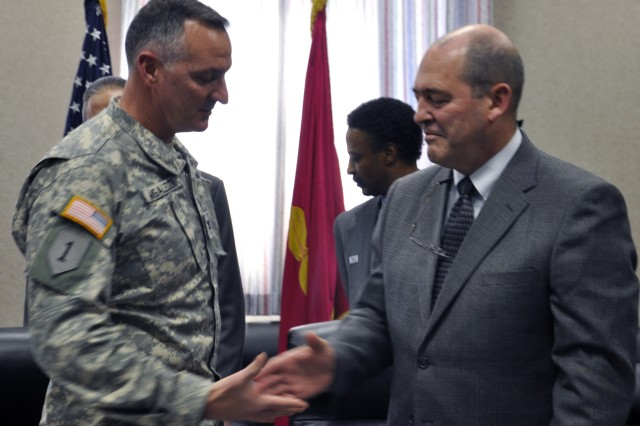 After the signing was complete, Arsenal Commander Col. Mark F. Migaleddi shakes hands with Sam H. Kupresin, vice president of Mandus Group.