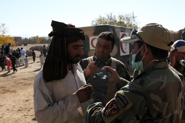 A villager takes instructions for the use of an inhaler from Afghan National Army Commando medics at a Village Medical Outreach Program event in Guzarah district, Nov. 5. The Commandos provided health-care assistance for men, women and children.
