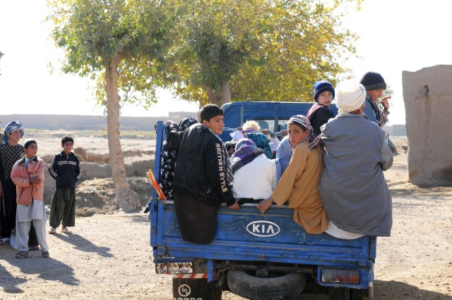 Family members drive up in a pick-up truck to receive medical care from Afghan National Army Commando medics at a Village Medical Outreach Program event in Guzarah district, Nov. 5. The Commandos provided health-care assistance for men, women and children.