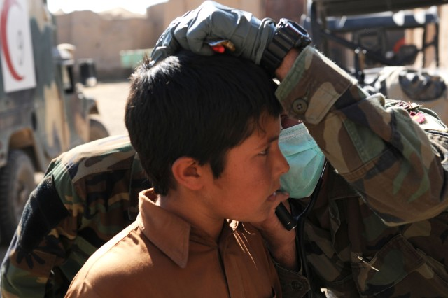 A village child receives an ear examination from an Afghan National Army Commando medic at a Village Medical Outreach Program event in Guzarah district, Nov. 5. The Commandos provided health-care assistance for men, women and children.