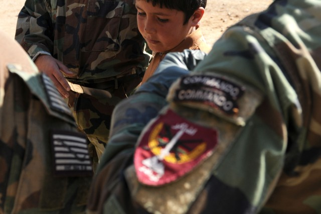A village child receives medical attention from Afghan National Army Commando medics at a Village Medical Outreach Program event in Guzarah district, Nov. 5. The Commandos provided health-care assistance for men, women and children.