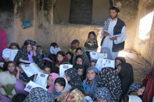 A teacher provides guidance and instructions to students as they participate in the Radio Literacy Program, Herat province, Nov. 7.  The RLP is an education based program run by the Government of the Islamic Republic of Afghanistan to provide basic reading and writing skills over the radio to all ages and genders of Afghan citizens.