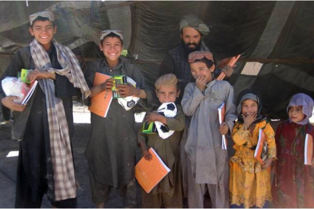 Children happily display their Radio Literacy Program books and other gifts handed out by the Afghan Local Police, Herat province, Nov. 7.  The RLP is an education based program run by the Government of the Islamic Republic of Afghanistan to provide basic reading and writing skills over the radio to all ages and genders of Afghan citizens.