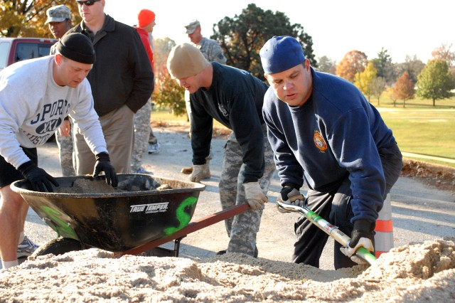 Directorate of Emergency Services Deputy Director Maj. Rob Ruskievicz, Platte County (Mo.) Sheriff's Department Capt. Paul Carrill and Fort Leavenworth Fire Capt. Kevin Seymour load and level a wheel barrow full of sand in a sand loading and dumping relay event, part of the First Responder Challenge, Nov. 9, 2011, in the Frontier Conference Center parking lot on Fort Leavenworth, Kan.